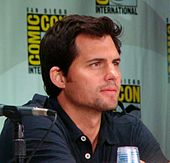 Color photograph of a white man with brown hair sitting in front of a ComicCon poster.