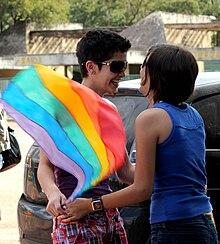 Twee vrouwen glimlachen naar elkaar en houden elkaars hand vast terwijl een van de vrouwen een LGBT-regenboogvlag vasthoudt