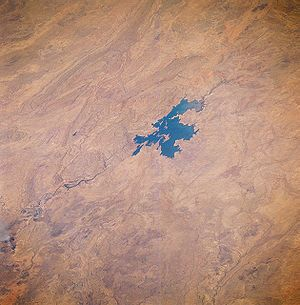 Lake Argyle - Lake Argyle seen from space, August 1985. The main channel of the Ord River (dark, meandering feature) north of the lake is visible as it drains northward, eventually emptying into the Joseph Bonaparte Gulf. Low, folded mountains can be identified east and west of this river valley.