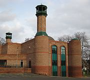 A striking modern building of two shades or red-brick with, on its left, two tall circular towers with minarets and a low entrance-building. The near end has two long thin windows with green panels and pointed tops to the right of the nearer tower. To the right of the windows is another, lower, tower with a small green dome. In the centre of the building, part of a larger dome can be seen. In the background are some trees and a red-brick Victorian terrace.