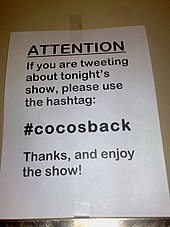A sign indicating which Twitter hashtag to use when tweeting about the performance.