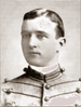 Head of a young white man with neatly combed hair wearing a jacket with lines of decorative piping running horizontally across the chest.