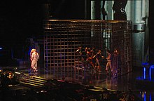 A huge cage, with the front open, standing on a stage. A number of dancers hold the rods of the cage and gesture. On the extreme right, the spotlight falls on a woman and a dancer greeting each other.