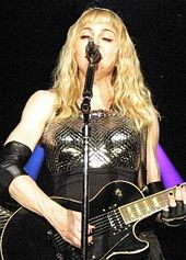 A woman in black clothing holding a guitar and standing behind a microphone stand with one arm extended straight into the air. In the background is a screen with shades of pink and purple.