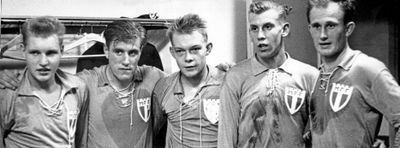 A black and white photograph of five football players standing beside each other in a locker room after a match. The players are noticeably tired; large sweat stains are visible on their shirts.