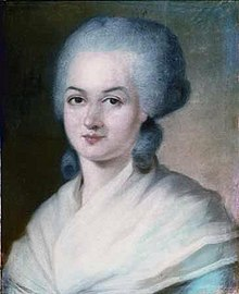 Portrait of a woman, showing her head, with a grey wig. Two large curls are sitting at the nape of her neck. Her shoulders are covered with a filmy, cream-coloured shawl.