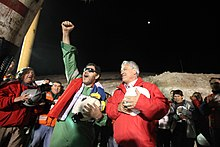 Color image of the mining leader and the Chilean President leading rescue workers in a rendition of the Chilean anthem.