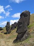 Large elongated stone heads on a grassy slope.