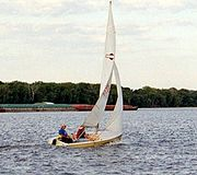 A sailboat (racing dinghy) and barge share the Mississippi River, USA.