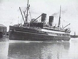 Black and white photograph of passenger ship with twin funnels, under steam