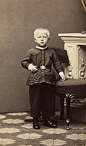 an unsmiling fair-haired child stands upright, his left hand resting on a stool, in front of an ornate fireplace.