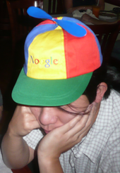 Asian man in his twenties wearing a blue, green, yellow and red propeller hat that says