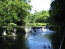 a river flowing over a weir, trees surrounding on a sunny day, blue sky, dark pool in foreground