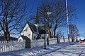 """Oppdal Church (kirke, kyrkje, """"Maret på Vang""""), Gauldal deanery (prosti), Oppdal municipality, Trøndelag county, Norway. Cruciform style 1651. Blue sky, snow, fence, graveyard, view, etc. 2019-03-19 lamp G.jpg"""