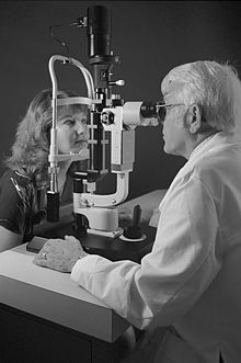 50d15b6c870 An optometrist examining the eyes of a patient with a slit lamp  biomicroscope