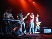 Four people on a stage. The first one with a plaid shirt and blue jeans, playing a keyboard. The second one wearing a black cap, a striped shirt and blue jeans, playing a bass guitar. The third one is a female wearing a gray hat, a pink shirt and blue jeans, holding a microphone. The fourth one, is wearing a gray shirt and blue jeans and is playing an electric guitar.