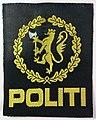 POLITI Politiet emblem tøymerke ermmerke armmerke 7,2 x 8,9 cm riksvåpen (gul riksløve norsk løve, hvitt økseblad, svart bunn) i åpen eikekrans (odalrune som knute) ca.1988-1995 (National Police of Norway, uniform patch, sleeve.jpg