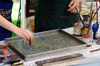 Paper marbling - Oil-based inks in a tank of water being prepared for marbling.