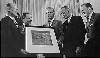 Mariner 4 - Jack N. James (center), JPL's Mariner 4 Project Manager, with a group in the White House presenting the spacecraft's famous picture Number 11 of Mars to US President Lyndon B. Johnson (center right) in July 1965.