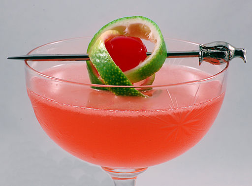 Pink Lady with a twist of lime, in a cocktail glass