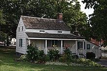 Photo couleur d'une maison en bois entourée d'une pelouse