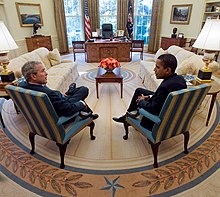 Obama meets with Bush in the Oval Office. Both sit at a distance in front of the presidential desk with their legs crossed and their backs on an angle toward the camera. They sit at right angles to each other.