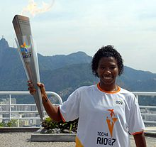 Soccer player Pretinha pictured holding the Pan-American Games torch