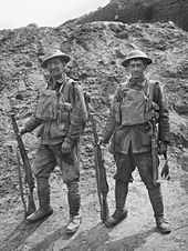 Black and white photo of two soldiers standing side by side in field uniform, each is wearing a steel helmet on their heads and load carriage equipment on their chests. Both are holding rifles in the right hands, with the weapon held vertically and the butt resting on the ground. In the background is an earthen mound.