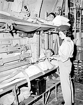 Black and white photo of a woman wearing military uniform standing next two men lying in bunk beds