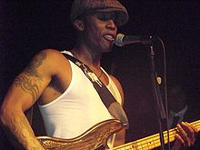 Saadiq playing bass guitar onstage