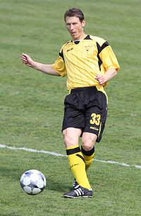 An in-action photograph of a man wearing a yellow football shirt, black shorts and yellow socks. The man has just passed the football to someone out of picture.