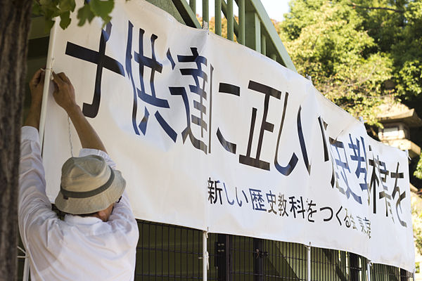 "A member of the Japanese Society for History Textbook Reform erects a banner reading ""[Give] the Children Correct History Textbooks"". Revisionists Yasukuni 1.jpg"