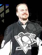 A Caucasian man smiling is shown from the waist up. He wears a black jersey with an anamorphic penguin playing ice hockey for the logo