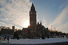A fine and ornate building with a huge clock tower fills the central part of the image. It appears directly in front of the sun giving it a dark silhouette-like setting. The scene is marked by white snow.