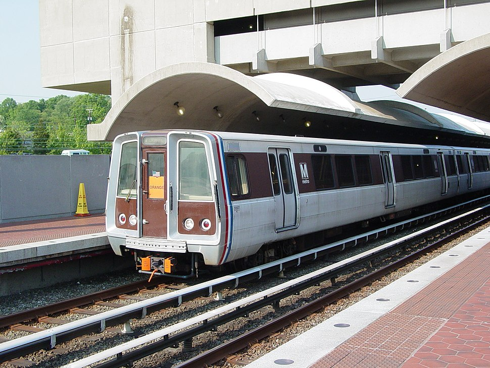 An exterior perspective view of a train, with its distinct brown and metallic design, at a station platform.