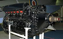 A front right view of a large, black-painted, piston aircraft engine with a prominent propeller shaft. A camouflaged military aircraft is parked behind.
