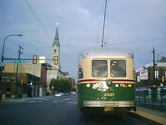 National Shrine of Saint John Neumann - Route 15 Trolley Passes St. Peter's at 5th and Girard (Spire to the left of trolley).