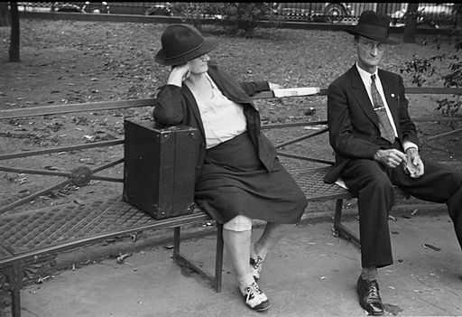 A woman with a case and a thin man sitting on a park bench in Jackson Square, New Orleans in 1935 (click to embiggen)