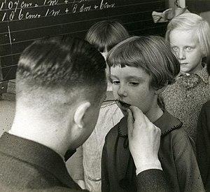 Pediatric dentistry - School dentist examining children's teeth. Netherlands, 1935.