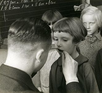 Pediatric dentistry - School dentist examining children's teeth. Netherlands, 1935.
