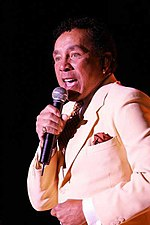 A man in a light-colored suit sings into a microphone