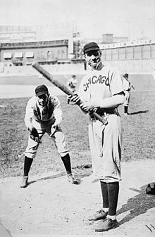 "Two men in baseball uniforms bearing the word ""Chicago"" on the chest—one is bent over prepared to catch a pitched ball, the other stands ready to swing a baseball bat."