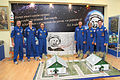 Soyuz TMA-22 prime and backup crews around a poster of Yuri Gagarin.jpg