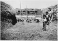 Spotted pigs in feedlot with women and children - NARA - 285641.tif