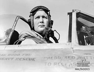Black and white photo of a man wearing a flying helmet sitting in the cockpit of an aircraft