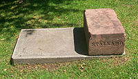 "A block of orange-pink stone on a concrete bed, surrounded by grass, with the name ""Stallard"" carved into the side facing the viewer"
