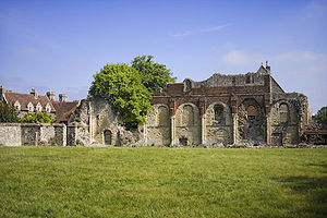 Landscape photo dominated by a field in front, surmounted by blue sky with white clouds. A ruined wall of a building crosses the center; in front a few stones can be seen piled atop each other.