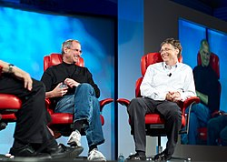 Two men in their fifties shown full length sitting in red leather chairs smiling at each other