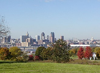 Minneapolis–Saint Paul - St. Paul, showing barges on the Mississippi River, the Capitol dome, and Minneapolis's skyline in the far background (right of St. Paul). In the lower right is a typical nineteenth century home. Taken from Indian Mounds Park.