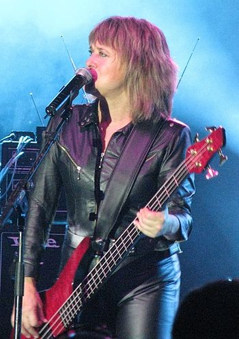 Suzi Quatro, wearing black leather, plays a ba...